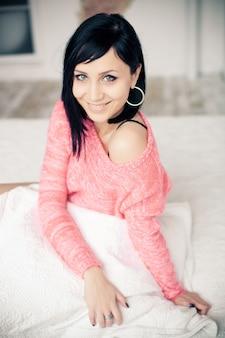 ピンクのセーターの美しい笑顔とブルネットの少女の肖像画は、彼女の手に枕を持って白いベッドに座っています