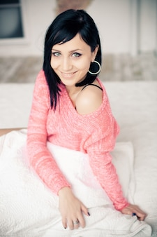 Brunette girl portrait with beautiful smile in a pink sweater sits on a white bed with the pillow in her hands