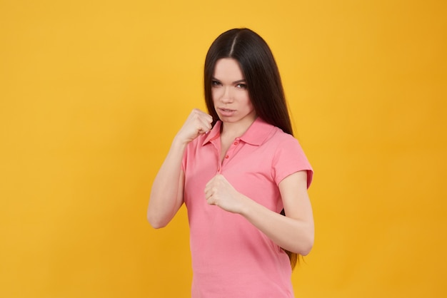 Brunette girl poses in fight stance isolated.