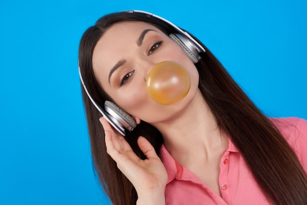 Brunette girl poses with bubble gum on blue background.