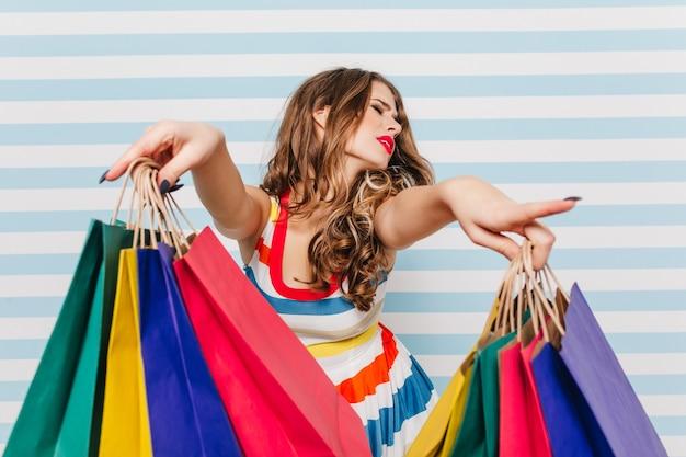 Девушка брюнетка позирует после больших продаж в магазинах. красивая молодая женщина, наслаждаясь покупками в выходные.