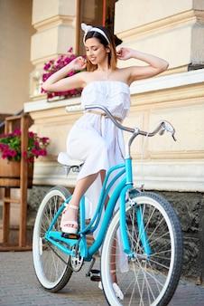 新鮮なマゼンタの花で飾られた古いアンティーク家の近くのターコイズブルーの自転車でポーズブルネットの少女