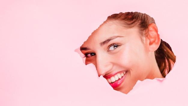 Brunette girl posing through a paper hole
