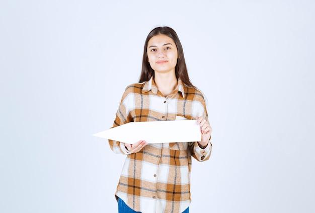 흰 벽에 빈 음성 화살표 포인터와 함께 포즈를 취하는 갈색 머리 소녀.