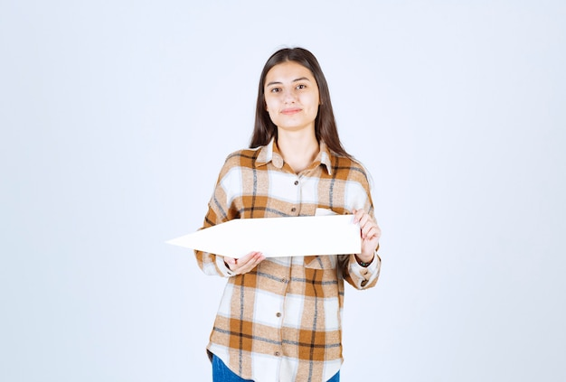 Brunette girl posing with empty speech arrow pointer on white wall.