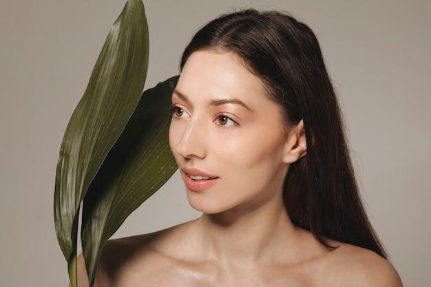 Brunette girl posing with exotic leaves
