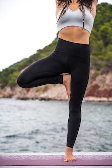 Брюнетка девушка упражнениями йоги на природе