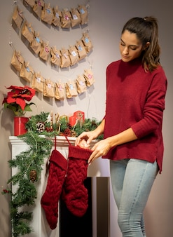 Brunette girl putting gift in christmas stocking