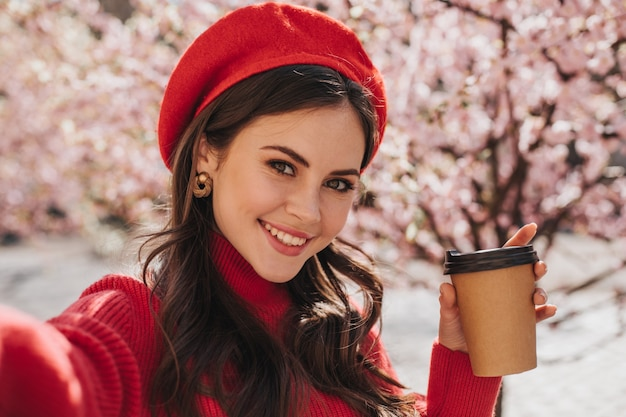 Brunette girl in red beret makes selfie with glass of coffee. green eyed woman in cashemere sweater widely smiling and holding tea cup