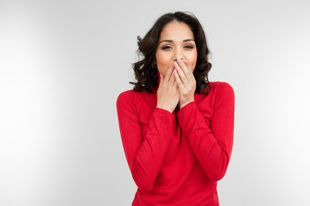 Brunette girl in a red tight-fitting sweater hides a secret by closing her mouth with her hand on a white background with copy space