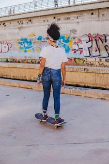 Brunette girl riding skateboard on street