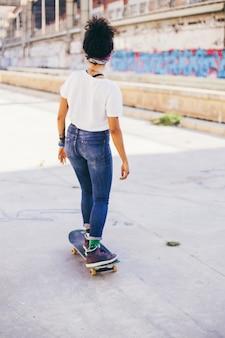 Brunette girl riding skateboard on street