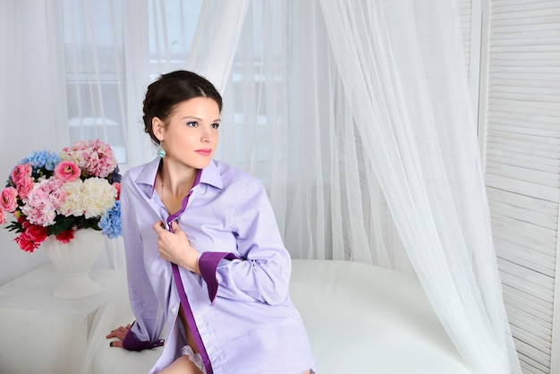 Brunette girl in a shirt sitting on a white bed