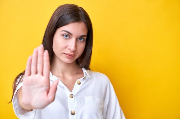 Девушка брюнетка показывает жест остановки руками, глядя в камеру с сильным лицом, изолированным на желтом фоне, держится на расстоянии