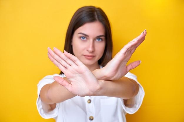 黄色の背景で隔離の強い顔でカメラを見て、手で停止ジェスチャーを示すブルネットの少女