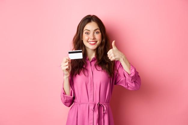 Девушка брюнетка показывает палец вверх и улыбается, рекомендуя банк, держа пластиковую кредитную карту, стоя у розовой стены. копировать пространство