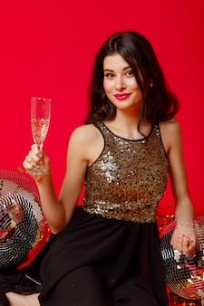 Брюнетка сидит в черном платье с золотыми блестками и держит в руках бокал шампанского