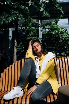 旧市街の中心部のベンチに座っているブルネットの少女。