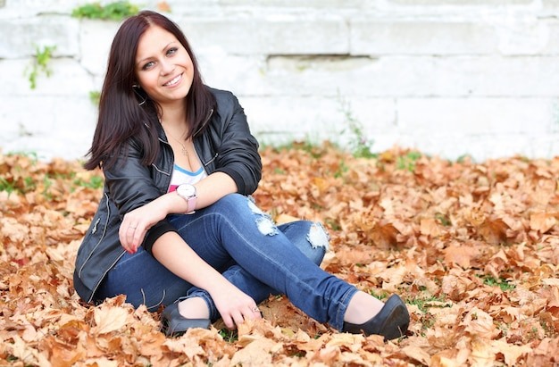 Девушка брюнетка сидит на осенних листьях