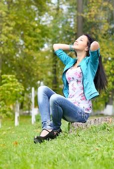 紅葉に座っているブルネットの少女
