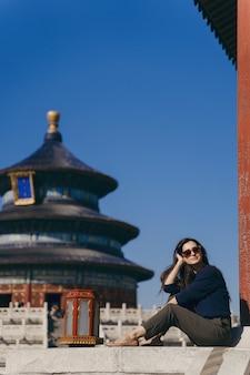 中国の天の寺院で階段に座っているブルネットの少女
