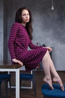 Девушка брюнетка сидит на столе дома в полосатом фиолетовом неформальном платье.