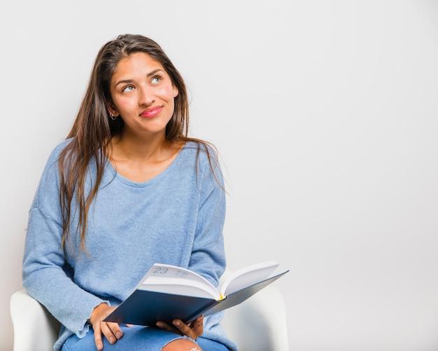 여자가 앉아서 책을 읽고
