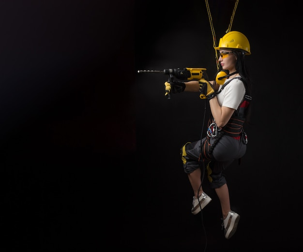 The brunette girl in special clothes and a worker in a helmet posing on a black background with a working tool ( girl hanging on climbing equipment construction works at height )