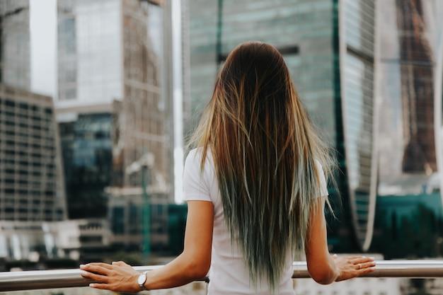 モスクワの高層ビルの前に立っているブルネットの少女。大都会の生活のコンセプト。ダウンタウンのコンセプト