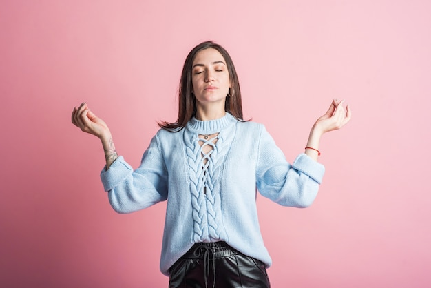 Brunette girl in the studio on a pink background shows hands gesture zen mudra
