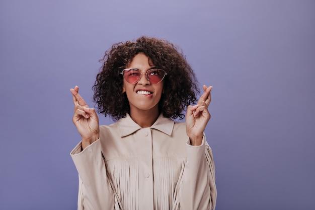 Ragazza bruna con gli occhiali da sole incrociò le dita sul muro viola