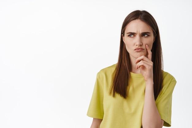 Брюнетка девушка думает с серьезным лицом, одетая в повседневную футболку, стоя на белом