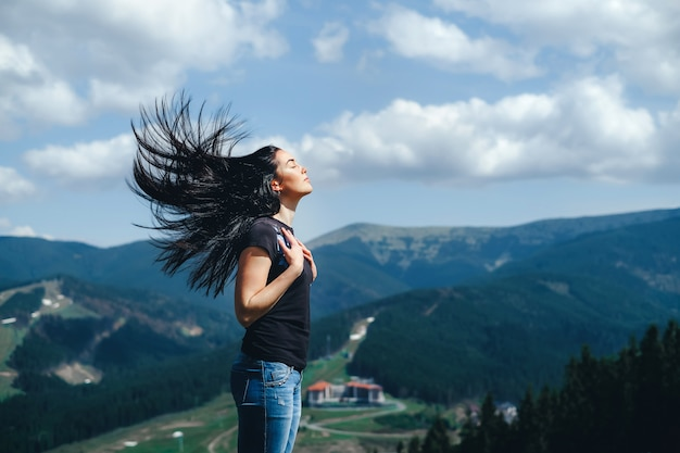 Brunette girl on the top of the mountain with streaming hair