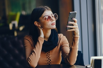 Brunette girl using her cell phone while sitting at a rastaurant for lunch
