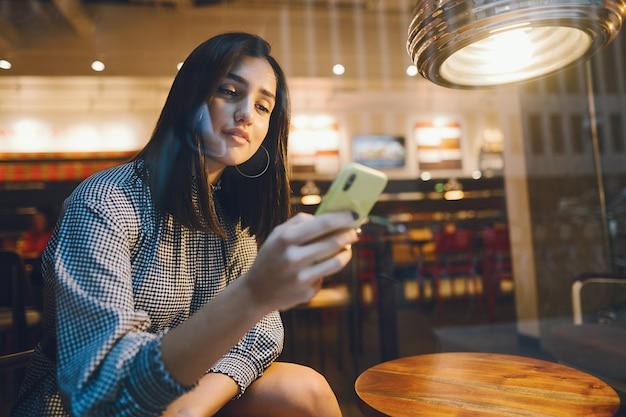 Брюнетка девушка, используя свой мобильный телефон, чтобы связаться с другом