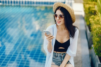 Brunette girl using her phone while relaxing by the pool
