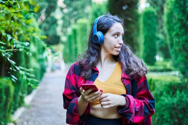 헤드폰으로 음악을 들으며 공원 정원을 걷는 갈색 머리 소녀