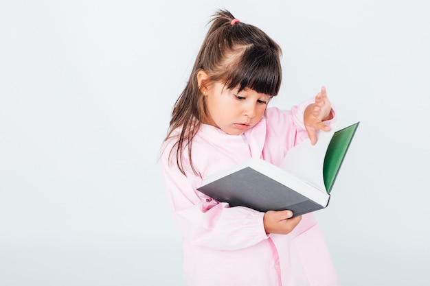 子供のエプロン読書を身に着けているブルネットの少女
