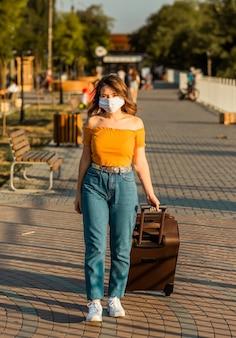 サージカルマスクを身に着けているブルネットの少女は、スーツケースを持って公園を散歩します。