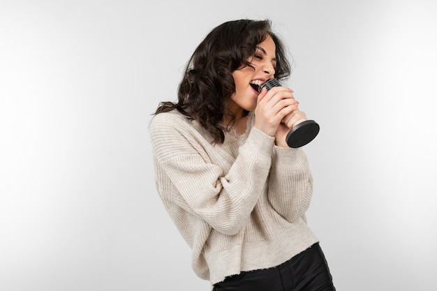 Brunette girl in a white sweater holds a retro microphone in her hand and sings a song on a white background.