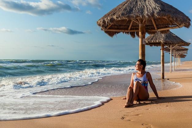 Девушка брюнетка с красивой фигурой позирует в купальнике на пляже возле зонтика от солнца. девушка в купальнике позирует на пляже