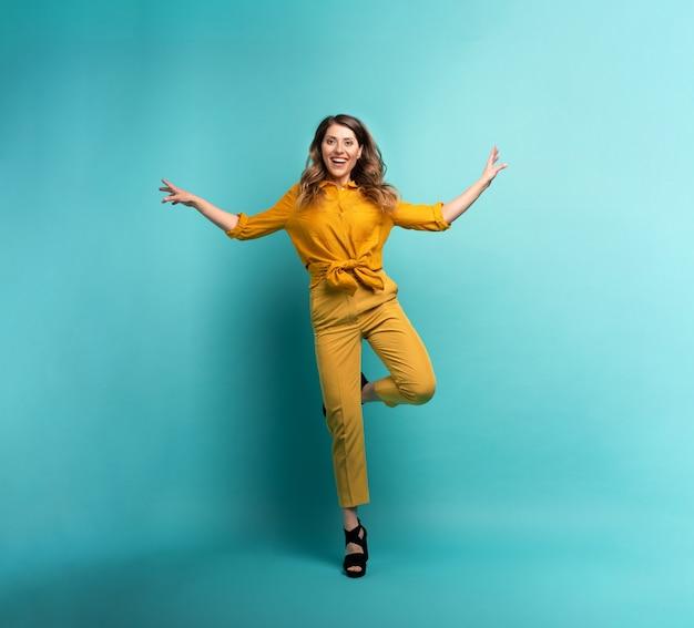 黄色の服を着たブルネットの少女は、シアンの背景を飛び越えます