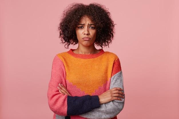 アフロの髪型のブルネットの少女は悲しい動揺を怒らせ、唇を吐き出し、否定的な感情に圧倒され、機嫌が悪く、腕を組んで立って、カラフルなセーターを着て、ピンクで隔離されます