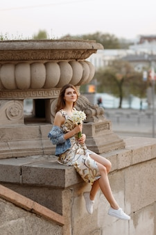 Brunette girl with a bouquet of flowers in the city on a summer walk. sunset