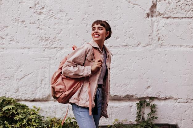 Ragazza bruna con zaino marrone in giacca beige in posa sul muro del muro bianco