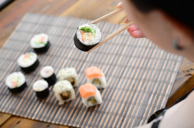 Brunette girl with chopsticks holds a sushi roll on a bamboo straw serwing mat background.