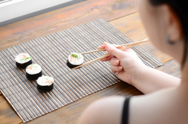 Brunette girl with chopsticks holds a sushi roll on a bamboo straw serwing mat background