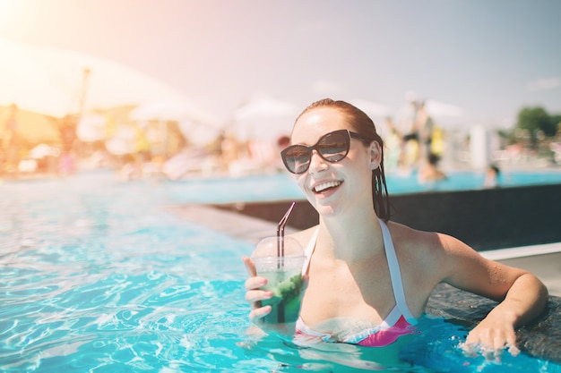 Brunette girl with cocktails relaxing in swimming pool. woman in bikini enjoying summer sun and tanning during holidays in pool with drink.