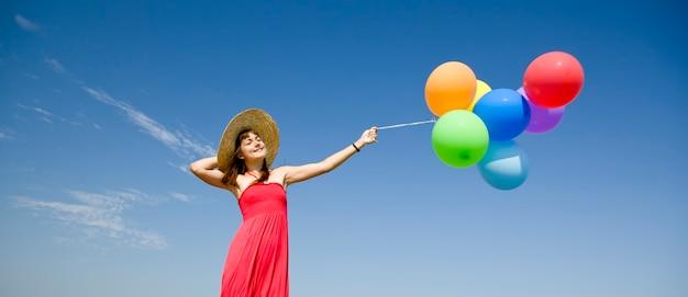 푸른 하늘에 색 풍선과 함께 갈색 머리 소녀입니다.
