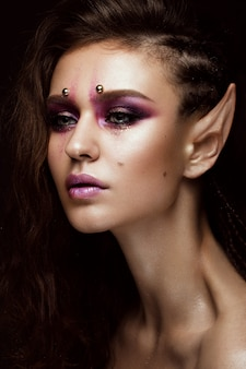 Brunette girl with a creative hairstyle braids, art make-up and the elf's ears. beauty face.